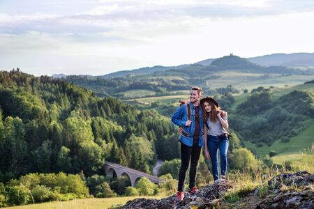 Young tourist couple travellers with backpacks hiking in nature, resting. Stock fotó