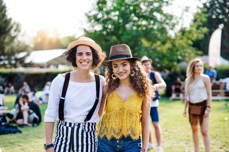 Portrait of two young women friends standing at summer festival.