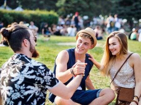Group of young friends sitting on ground at summer festival. Stock fotó