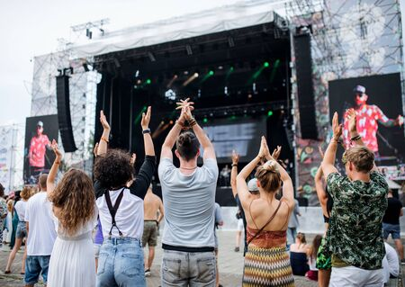 Rear view of group of young friends dancing at summer festival. Stock fotó