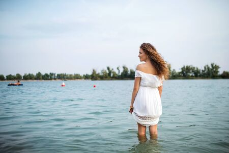 Rear view of young woman at summer festival, standing in lake. Stock fotó