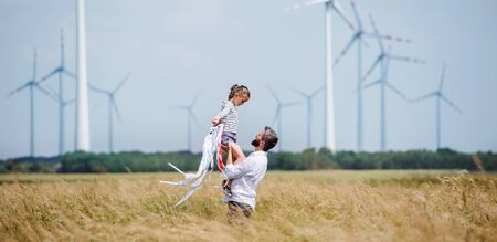 Mature father with small daughter standing on field on wind farm.