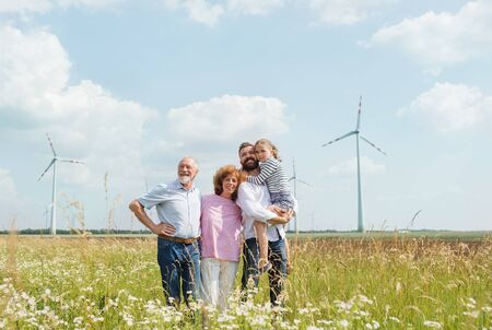 Multigeneration family standing on field on wind farm. Stock fotó