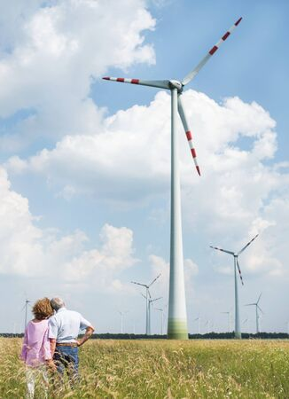 Rear view of senior couple walking on field on wind farm. Copy space.