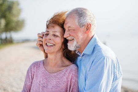 Close-up of senior couple on a holiday on a walk, hugging. Stock fotó