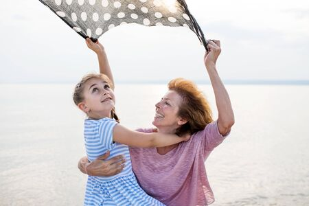 Small girl with grandmother on a holiday by the lake, having fun. Stock fotó