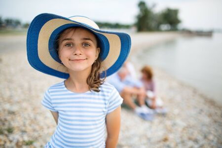 Front view of small girl on a holiday by the lake, looking at camera.