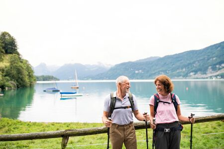 Senior pensioner couple with nordic walking poles hiking in nature, resting.