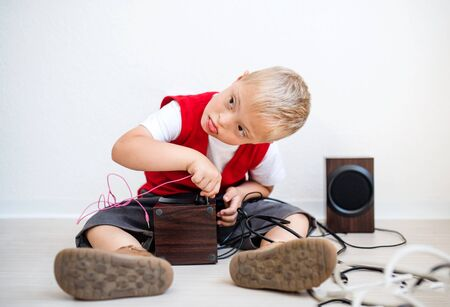 A portrait of down-syndrome school boy sitting on the floor, using loudspeakers.