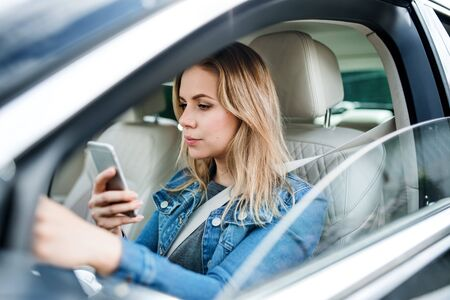 A young woman driver sitting in car, using smartphone.