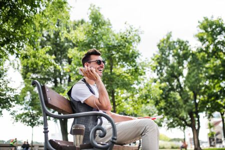 Young blind man with smartphone sitting on bench in park in city, calling. Banque d'images