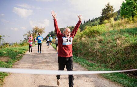 Corredor de hombre Senior cruzando la línea de meta en una competencia de carrera en la naturaleza.