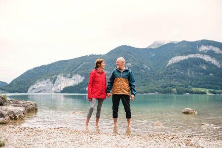 A senior pensioner couple hikers standing barefoot in lake in nature. Zdjęcie Seryjne