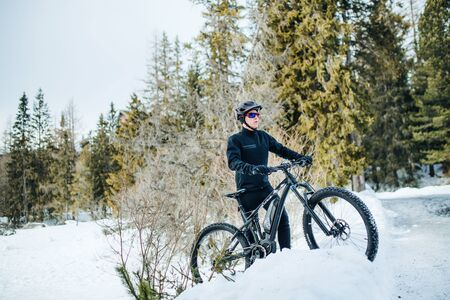 A mountain biker riding in snow outdoors in winter nature.