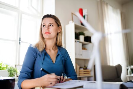 Young woman sitting at the desk indoors in home office, working.