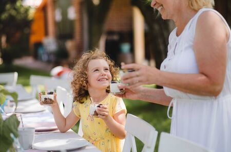 Small girl with grandmother outdoors on garden party in summer, eating. Stock Photo