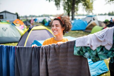 Young woman hanging towels at summer festival or camping holiday.
