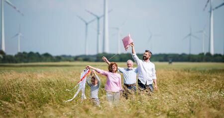 Multigeneration family standing on field on wind farm, playing with kite. Banque d'images