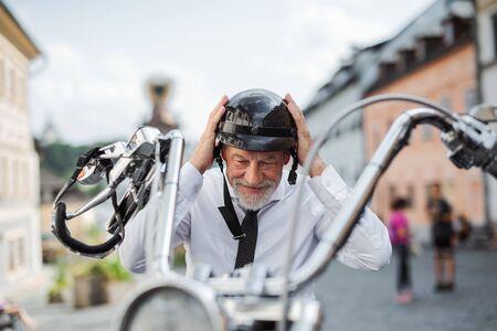 Un anziano uomo d'affari con una moto in città, che indossa il casco.