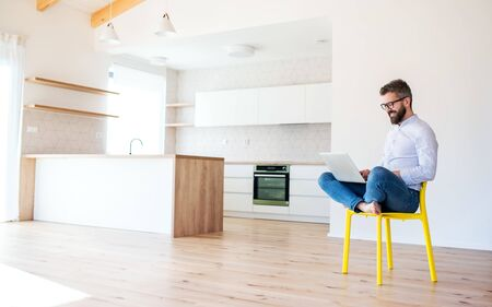 A mature man sitting on chair in unfurnished new house, using laptop.