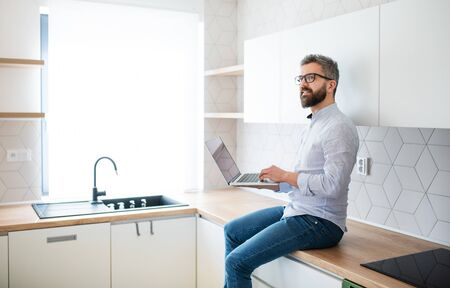 A mature man with laptop sitting in kitchen in unfurnished new house. Stock fotó