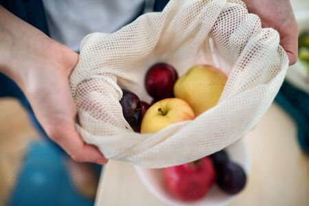 Midsection of woman holding fruit in reusable bag indoors at home, sustainable lifestyle concept.
