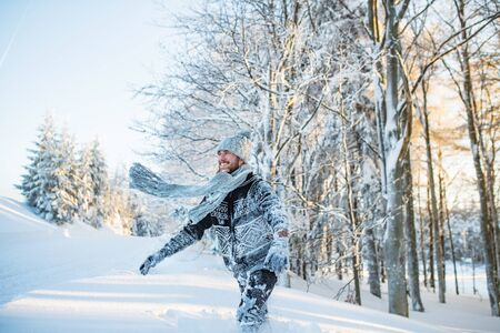 Young man having fun in snow outdoors in winter. Banque d'images