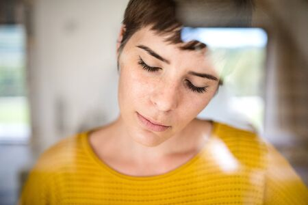Front view of sad young woman standing indoors at home, close-up.