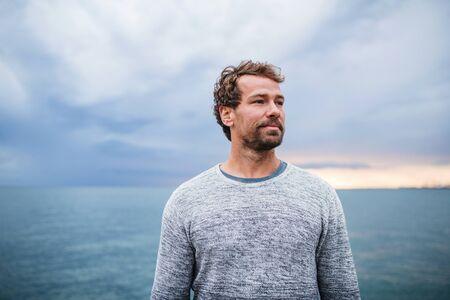Mature man standing outdoors on beach at dusk.