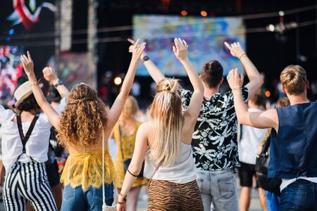 Rear view of group of young friends dancing at summer festival.