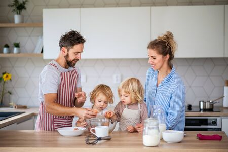 Young family with two small children indoors in kitchen, cooking. Stock Photo - 137159938