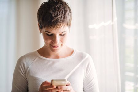 Young woman with smartphone standing indoors at home, texting.