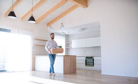Mature man walking in unfurnished house, holding a moving box. Archivio Fotografico