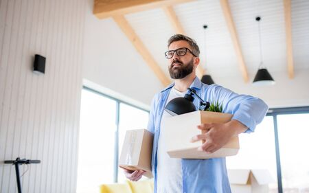 Mature man with boxes moving in new unfurnished house, walking. Stock Photo