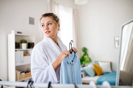 Young woman indoors at home in the morning, choosing clothes to wear. Banque d'images