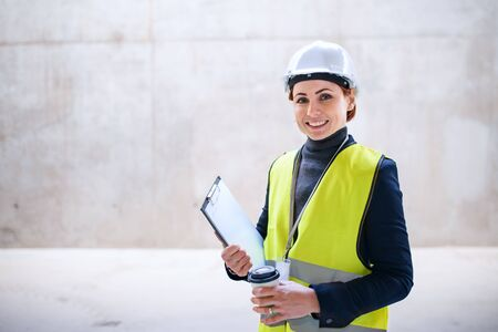 A woman engineer standing against concrete wall on construction site.