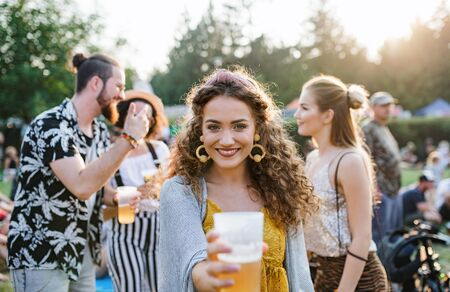 Group of young friends with drinks at summer festival, standing. Stock fotó