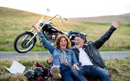 Wesoły senior para podróżujący z motocyklem na wsi.