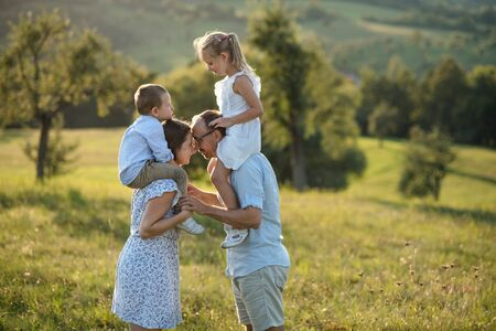 Young family with two small children standing on meadow outdoors at sunset.