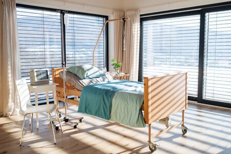 Empty, adjustable bed in room in private modern hospital.