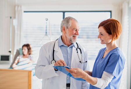 Portrait of senior male doctor standing in hospital room, talking to a nurse. Foto de archivo