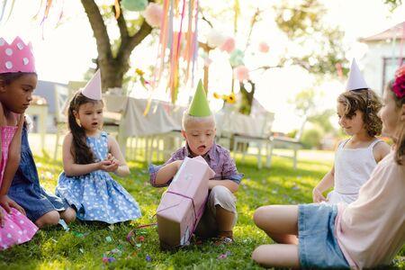 Niño con síndrome de Down con amigos en la fiesta de cumpleaños al aire libre, abriendo regalos. Foto de archivo