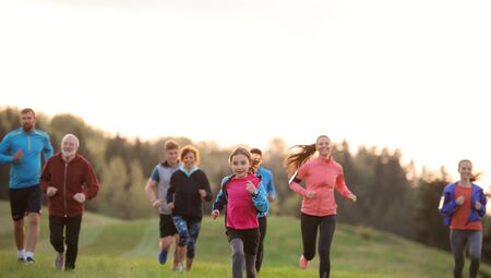 A large group of people cross country running in nature. Stock Photo