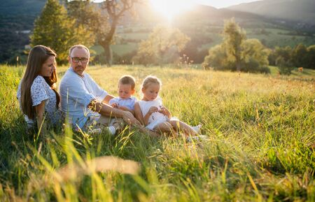 Young family with two small children sitting on meadow outdoors at sunset. Stok Fotoğraf