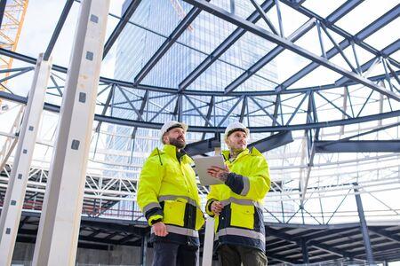 Ingenieros de hombres de pie al aire libre en el sitio de construcción, usando tableta.