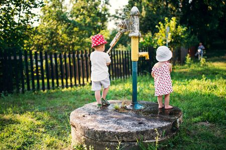 A rear view of toddler children standing outdoors in garden in summer. Stockfoto - 139861200