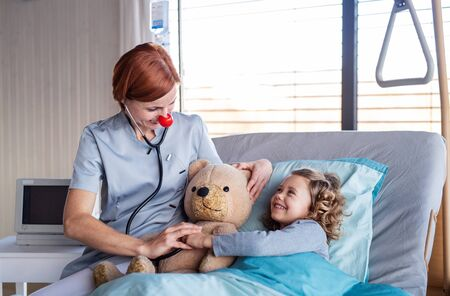 Friendly female doctor examining small girl in bed in hospital. Stock fotó