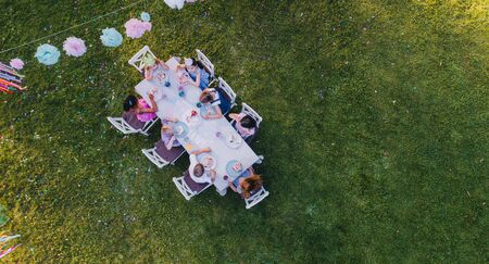Aerial view of small children sitting at the table outdoors on garden party.