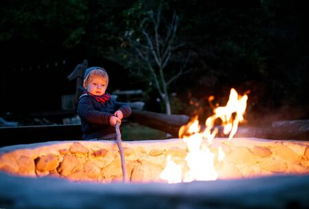 A toddler boy standing and playing by open fire outdoors in garden in summer.