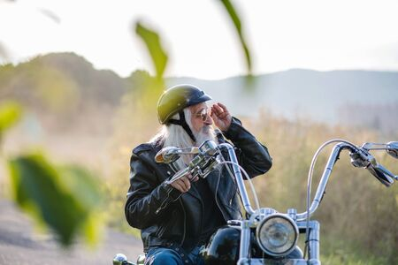 A senior man traveller with motorbike and sunglasses in countryside. Stock Photo